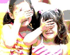 Two girls cover their eyes with their hands
