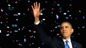President Obama waving to supporters as red, white and blue confetti falls